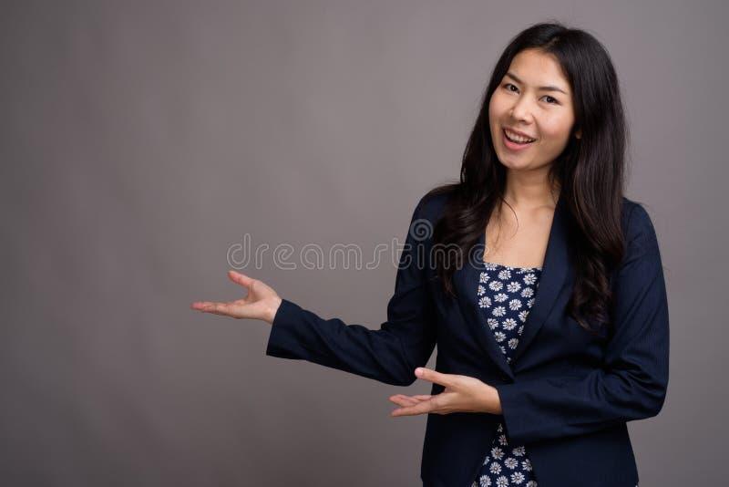 Азиатская женщина нося голубой свитер платья и кардигана против серого цвета стоковое фото