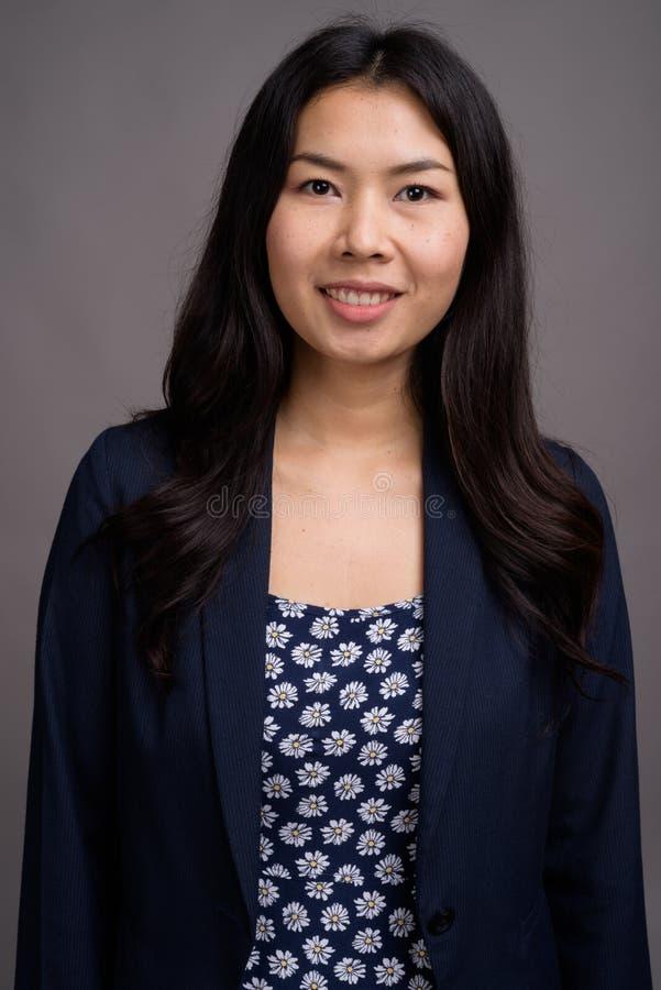 Азиатская женщина нося голубой свитер платья и кардигана против серого цвета стоковая фотография rf