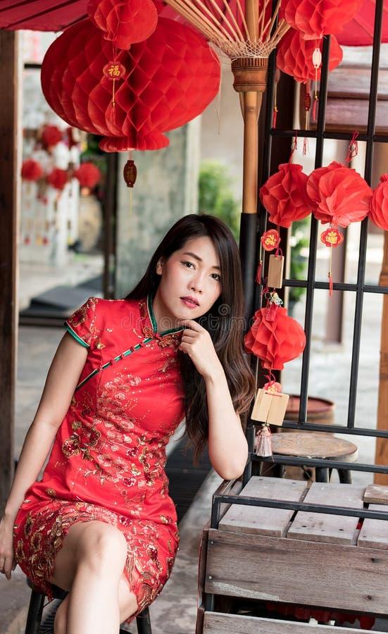 Азиатская женщина нося красное традиционное платье в китайском фестивале Нового Года стоковая фотография