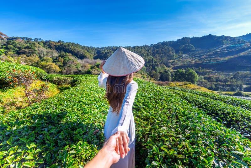 Азиатская женщина нося человека удерживания культуры Вьетнама руку традиционного и водя его к полю зеленого чая стоковые изображения