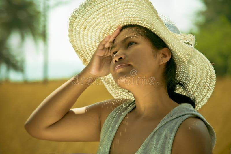 Азиатская женщина нося шляпу внешнюю на горячий солнечный летний день стоковое изображение rf