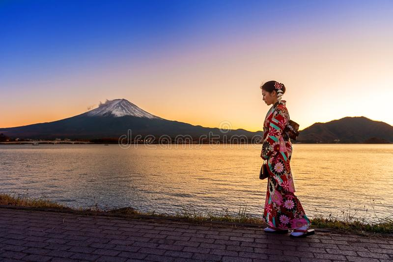 Азиатская женщина нося японское традиционное кимоно на горе Фудзи Заход солнца на озере Kawaguchiko в Японии стоковые изображения rf