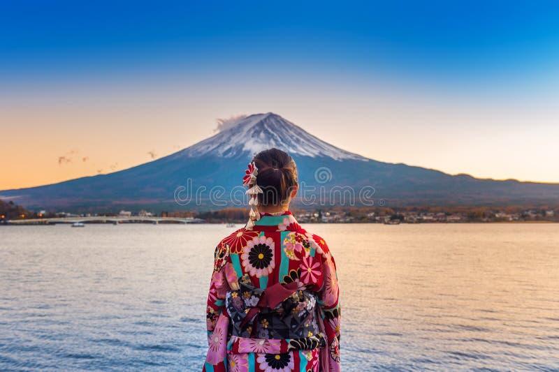 Азиатская женщина нося японское традиционное кимоно на горе Фудзи Заход солнца на озере Kawaguchiko в Японии стоковое изображение