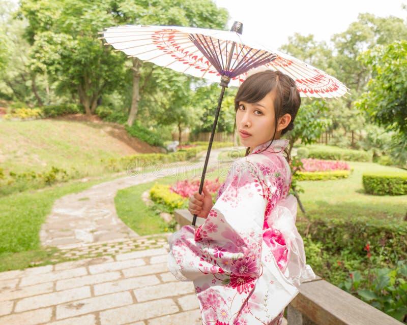 Азиатская женщина нося yukata и держа зонтик в японце стоковое изображение rf