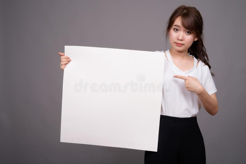 Азиатская женщина показывая пустую белую доску с copyspace стоковая фотография rf