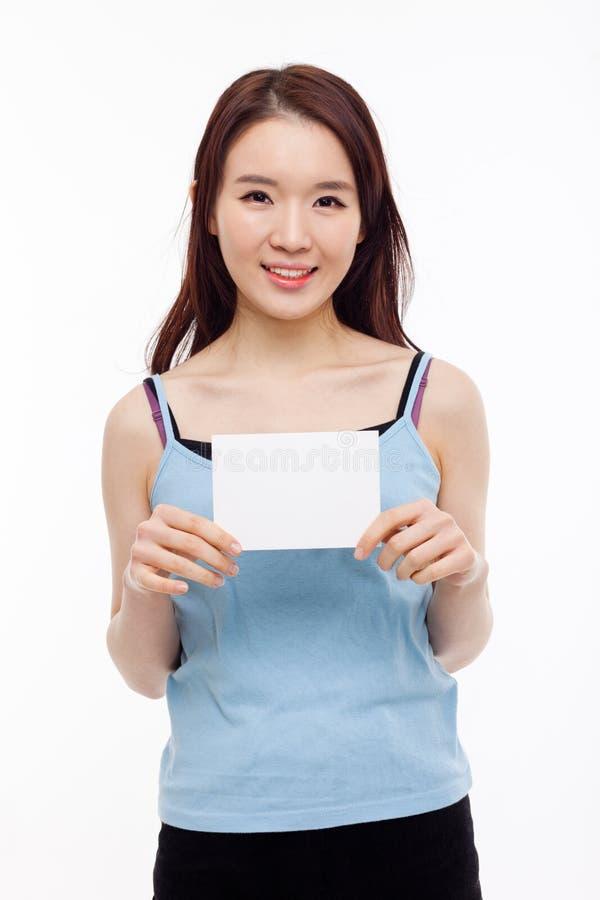 Азиатская женщина показывая пустую карточку стоковая фотография rf