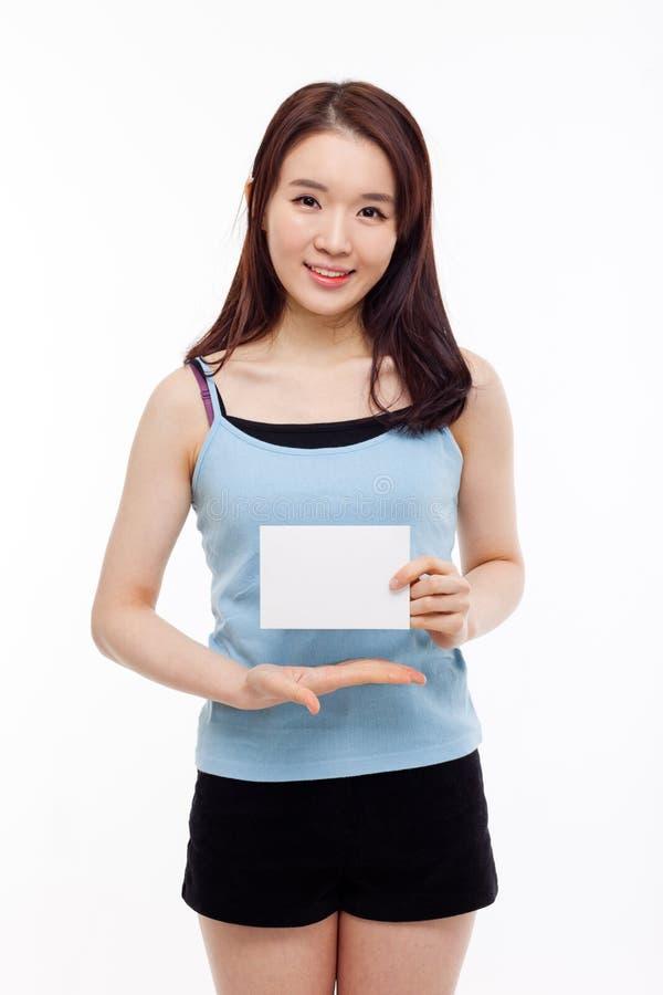 Азиатская женщина показывая пустую карточку стоковая фотография
