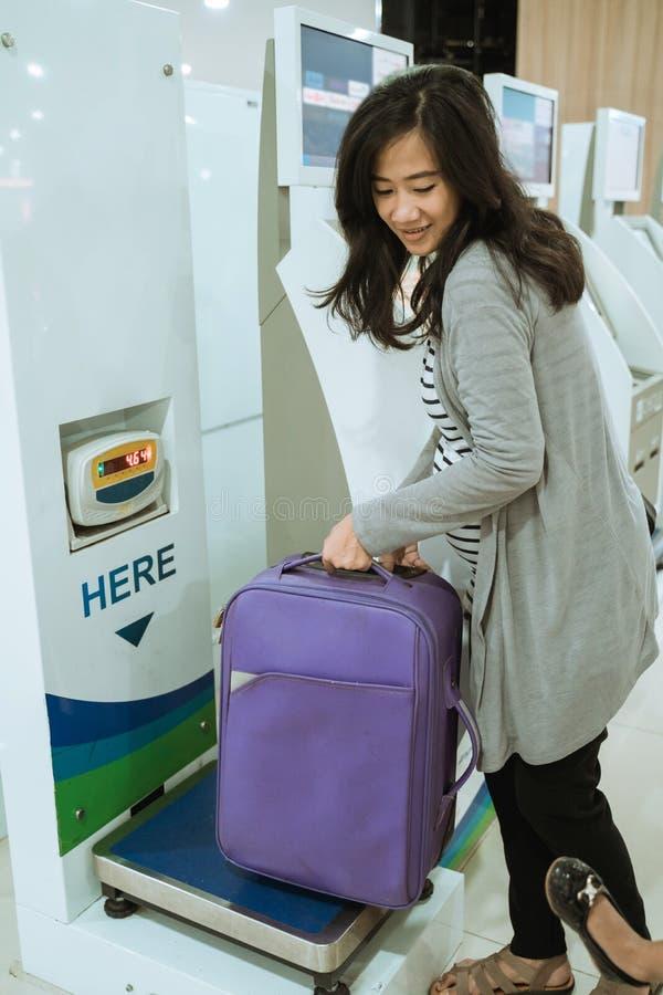 Азиатская женщина положила чемодан в масштаб багажа стоковое изображение