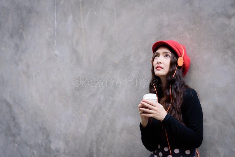 Азиатская женщина портрета с красной шляпой и черными одеждами имеет держать стоковая фотография