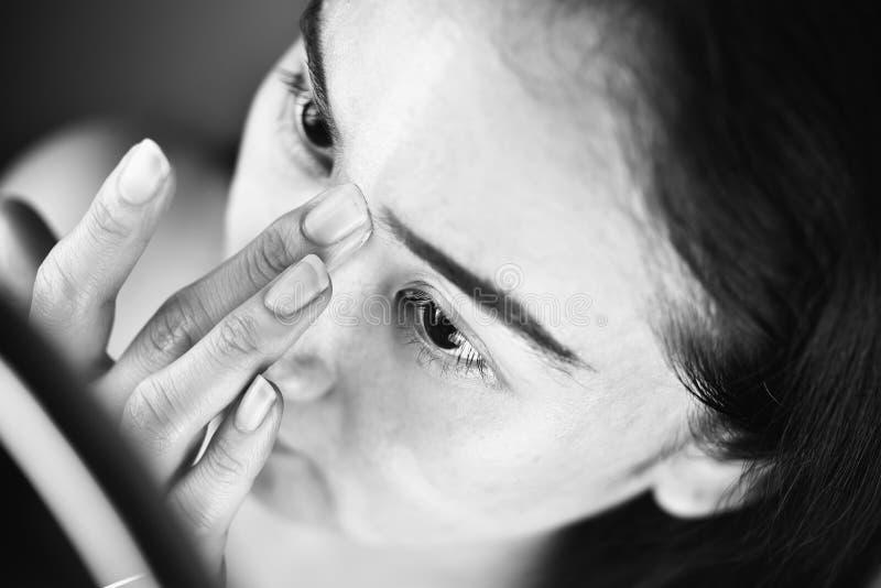 Азиатская женщина прикладывая макияж косметик и используя concealer коррекции цвета стоковое фото rf