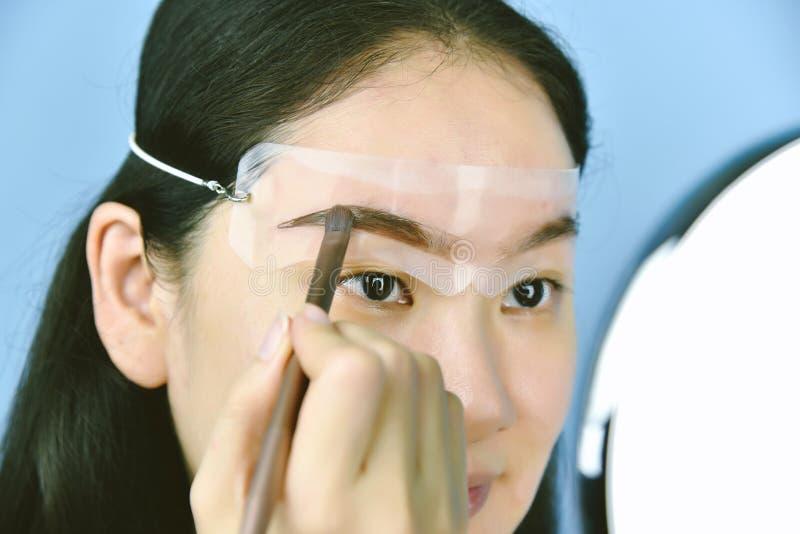 Азиатская женщина прикладывая макияж косметик, пользу ремня шаблона бровей главную для формировать стоковое фото