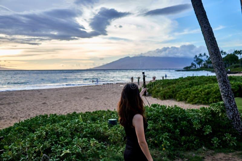 Азиатская женщина принимая selfy на пляж около курорта в Мауи Гаваи, США стоковая фотография