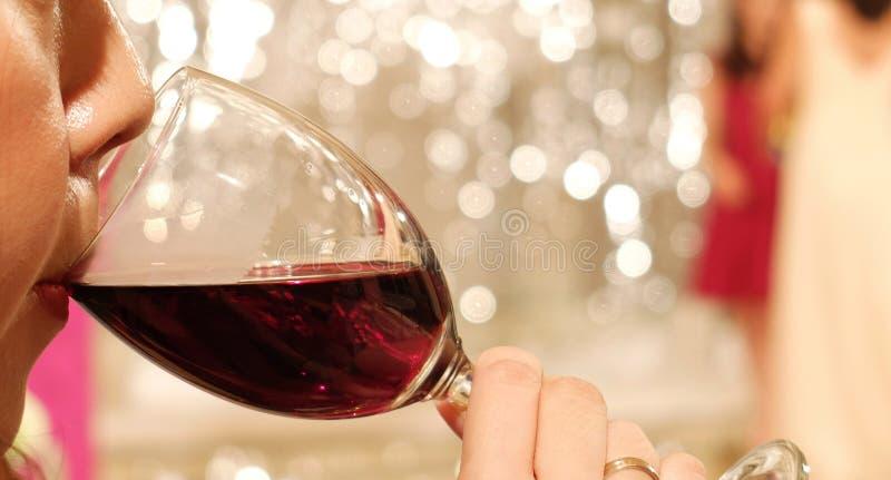 Азиатская женщина при губная помада Sipping красное вино в стекле на угле стоковые изображения rf
