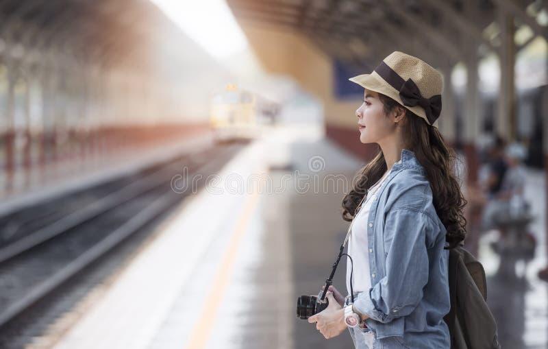 Азиатская женщина путешественника рюкзака при камера стоя на st поезда стоковое изображение rf