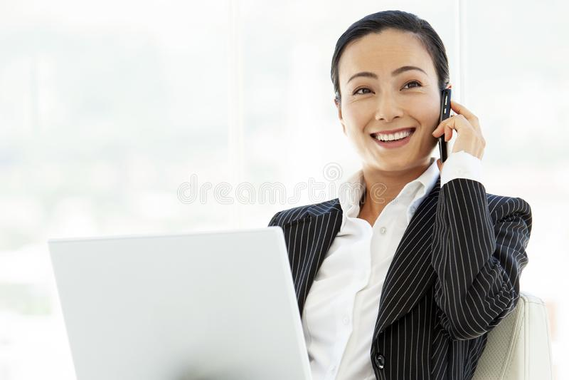 Азиатская женщина руководителя бизнеса с ноутбуком и смартфоном стоковое фото
