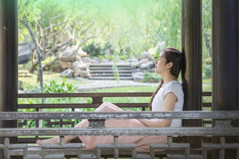 Азиатская женщина сидя на деревянном стуле в общественном парке для для того чтобы ослабить время стоковая фотография rf