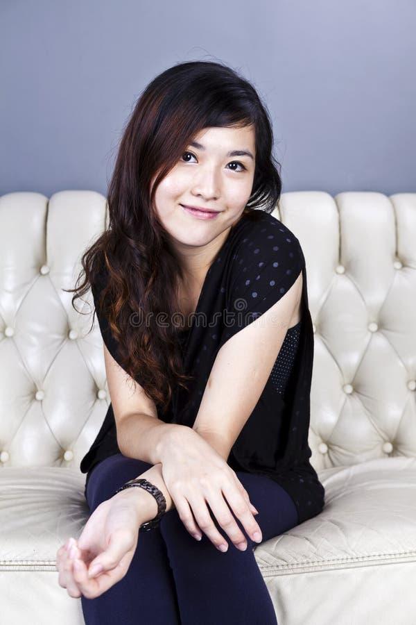 Азиатская женщина сидя на софе стоковые фото