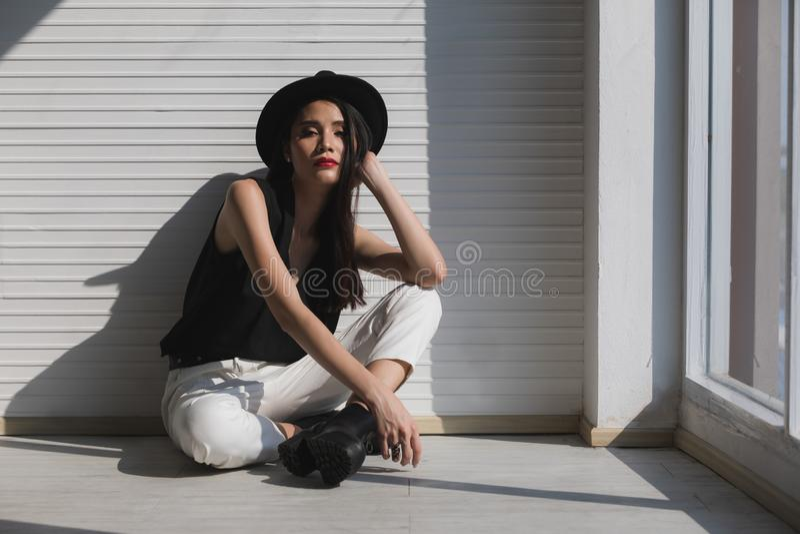 Азиатская женщина сидя около окна стоковое изображение