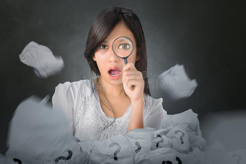 Азиатская женщина смотря через лупу сверх комкает бумагу стоковые изображения rf