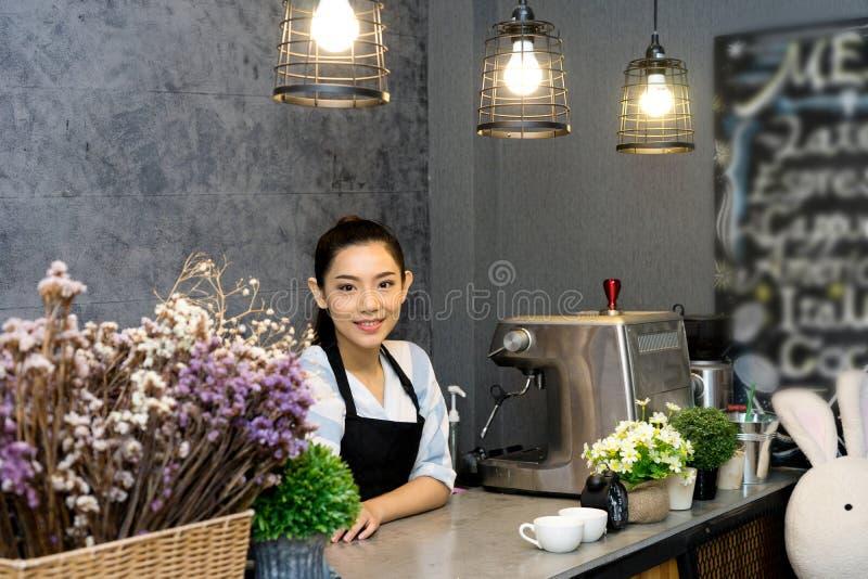 Азиатская женщина стоя в счетчике barista кофейни стоковое фото rf