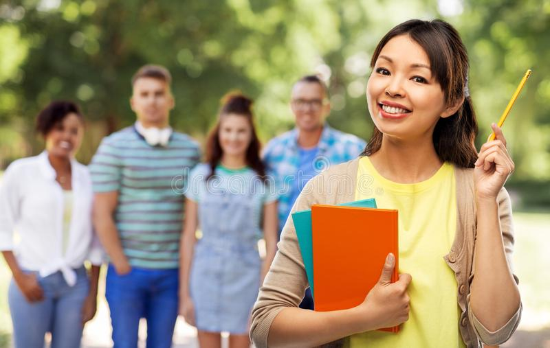 Азиатская женщина студента с книгами и карандашем стоковое фото
