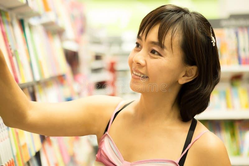 Азиатская женщина счастливая для того чтобы выбрать некоторую книгу на книжных полках стоковые фотографии rf