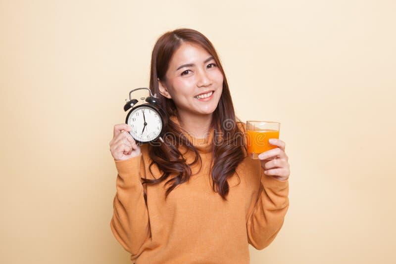 Азиатская женщина с апельсиновым соком питья часов стоковые изображения