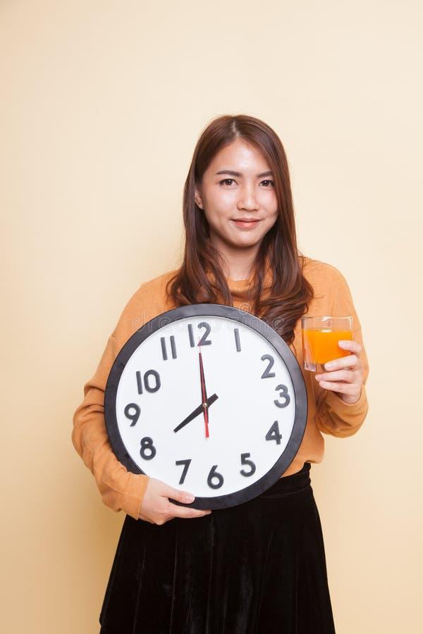 Азиатская женщина с апельсиновым соком питья часов стоковое изображение