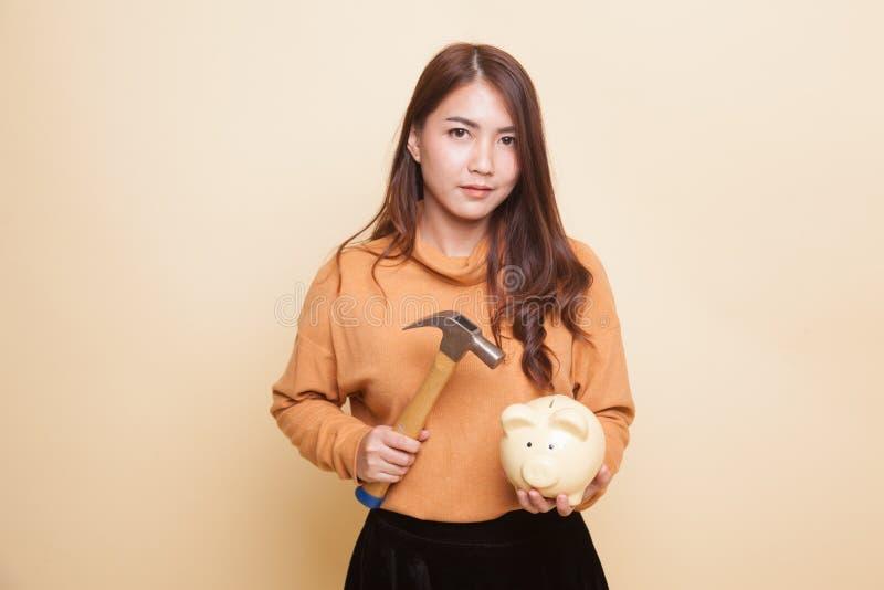 Азиатская женщина с банком и молотком монетки свиньи стоковая фотография