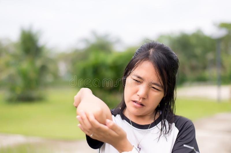 Азиатская женщина с болью в локте после разминки на открытом воздухе, женской руки касаясь ее тягостному рычагу, стороне выборочн стоковое фото rf
