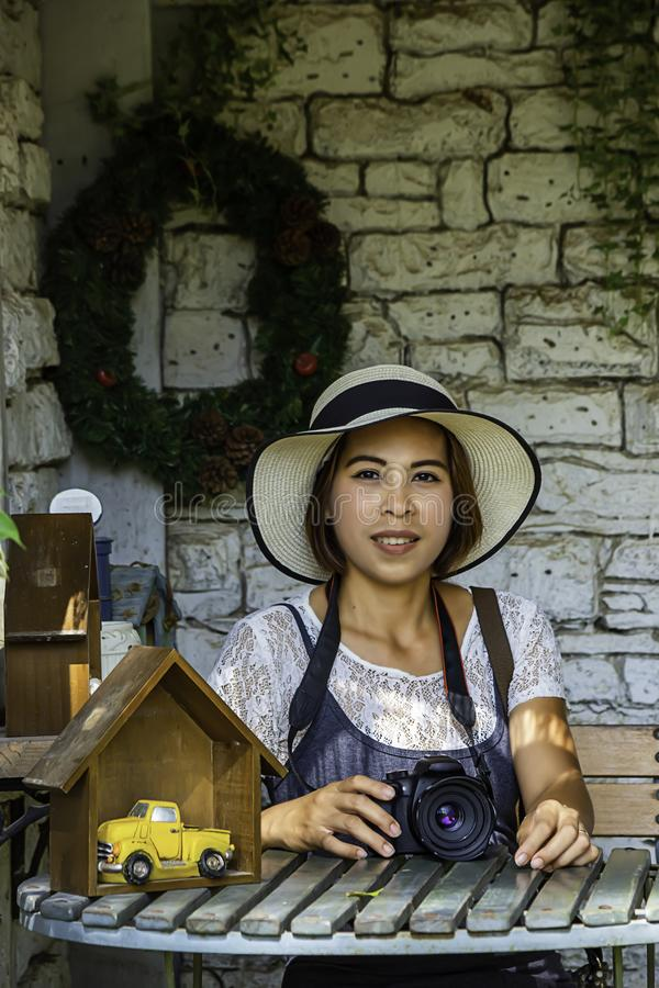 Азиатская женщина с короткими волосами нося шляпу и камеру на кирпичной стене предпосылки таблицы белой стоковые изображения