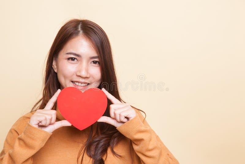 Азиатская женщина с красным сердцем стоковые изображения