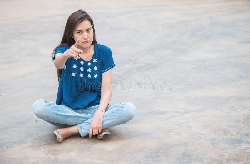 Азиатская женщина с сердитой эмоцией стороны на запачканной конкретной предпосылке текстуры пола стоковое фото rf