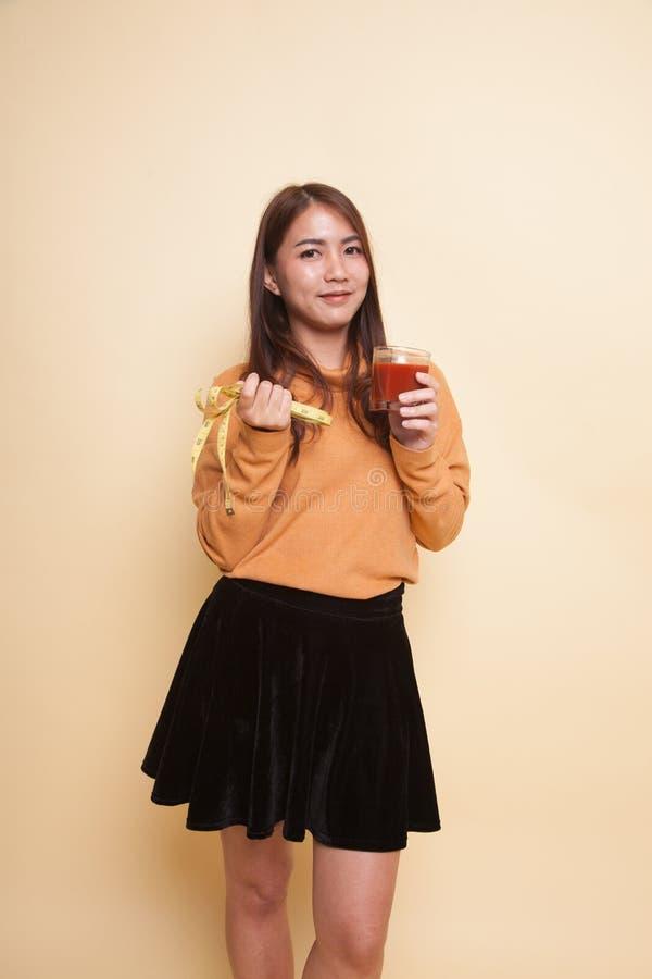 Азиатская женщина с соком томата и измеряя лентой стоковая фотография