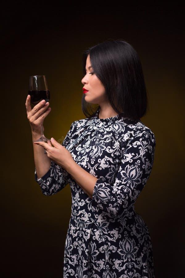 Азиатская женщина с стеклом красного вина стоковые изображения rf