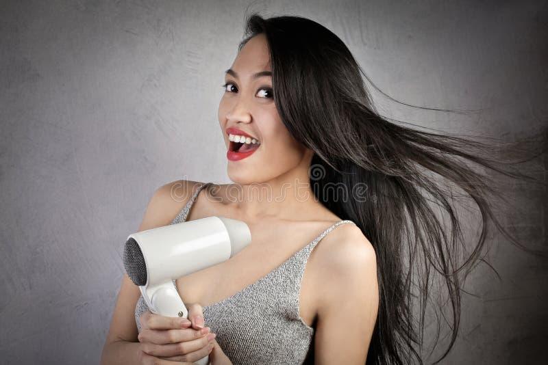 Азиатская женщина с haurdryer стоковое фото rf