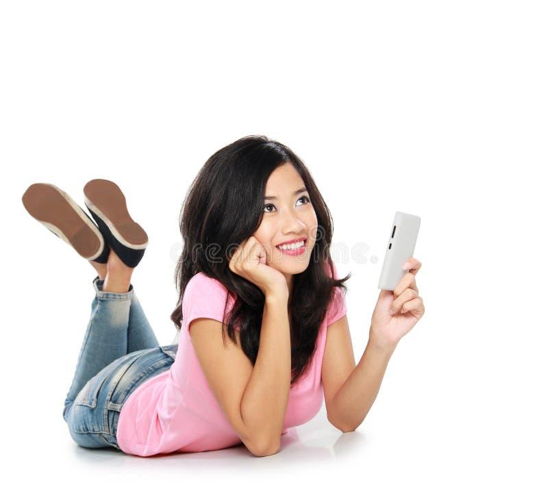 Азиатская женщина думая что сказать в текстовом сообщении стоковое фото rf