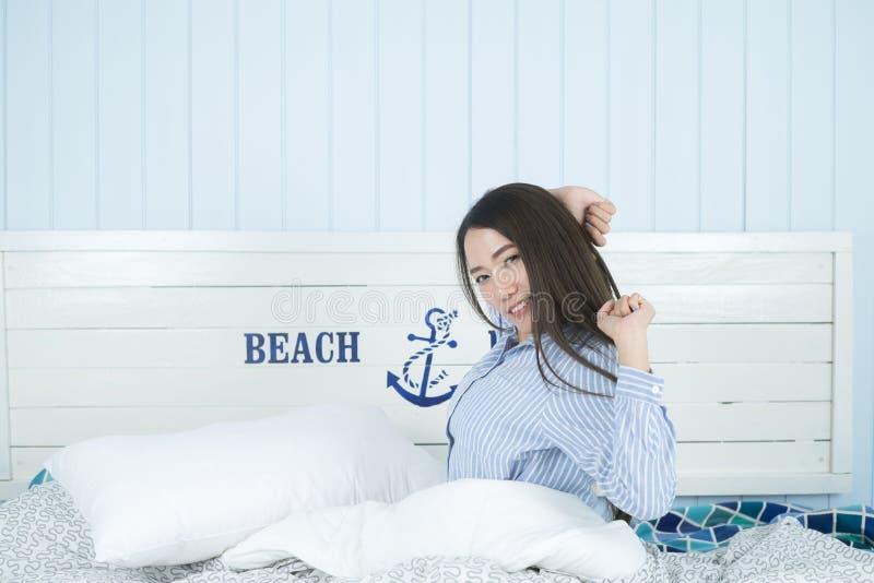 Азиатская женщина усмехаясь и протягивая в утре на спальне после просыпать вверх стоковые изображения rf