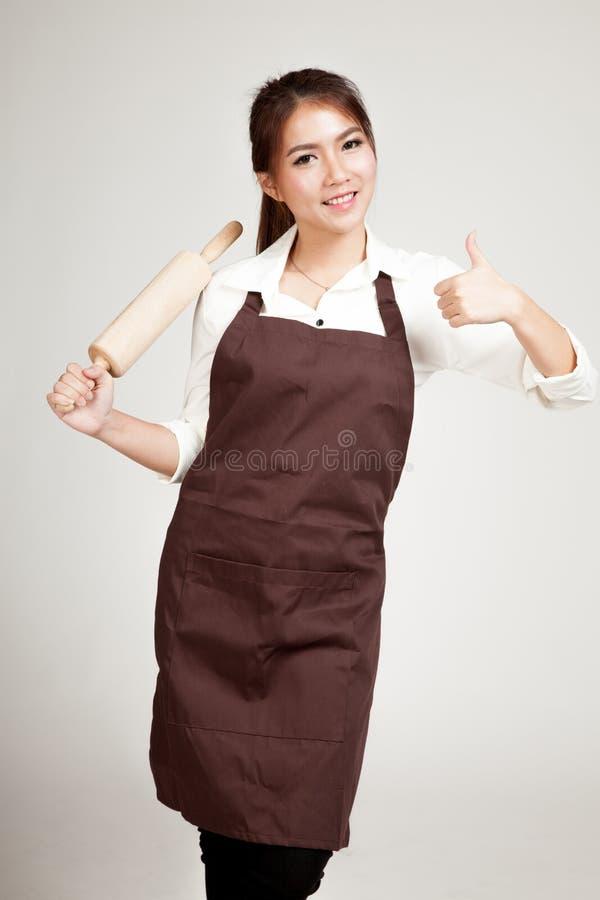 Азиатская женщина хлебопека в больших пальцах руки рисбермы вверх с деревянной вращающей осью стоковые фото