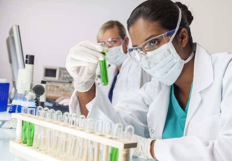 Азиатская индийская женская пробирка зеленого цвета ученого лаборатории стоковые изображения rf