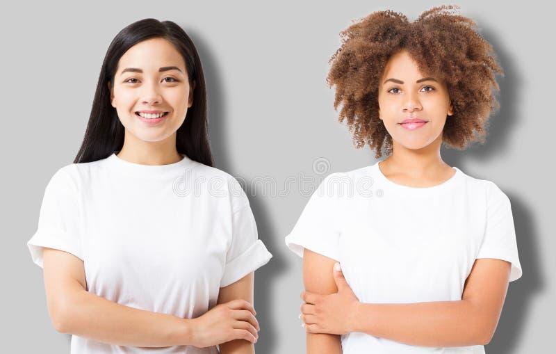 Азиатская и Афро-американская девушка в пустой футболке шаблона изолированной на серой предпосылке Женщины в футболке с космосом  стоковая фотография rf