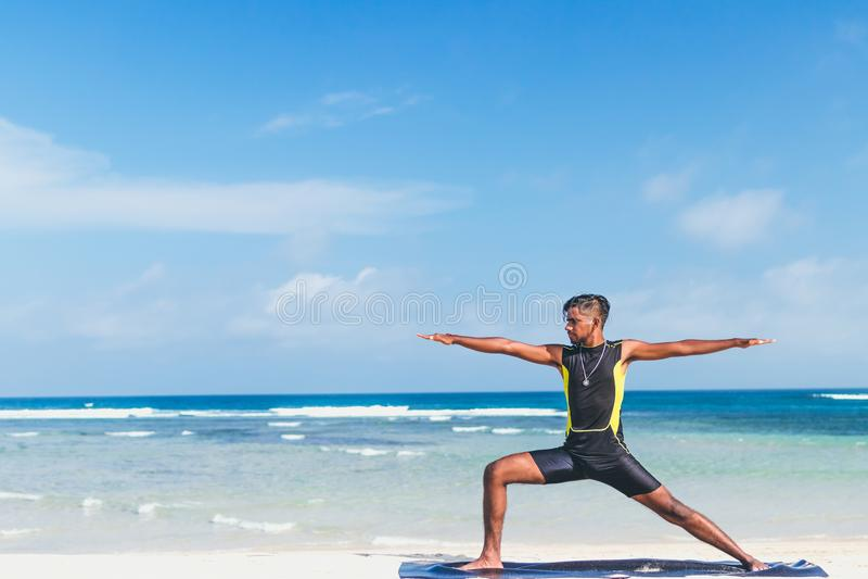 Азиатская йога практики человека йоги на пляже с ясной предпосылкой голубого неба Yogi на тропическом пляже острова Бали стоковые фотографии rf