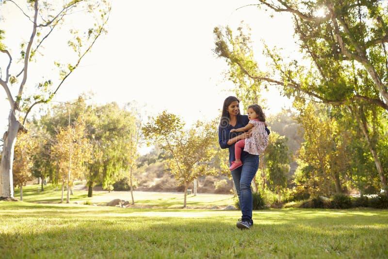 Азиатская кавказская женщина нося ее молодую дочь в парке стоковая фотография rf