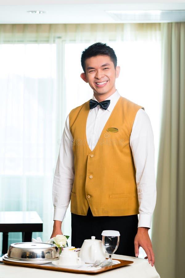 Азиатская китайская еда сервировки кельнера гостиничного сервиса в гостинице стоковые фото