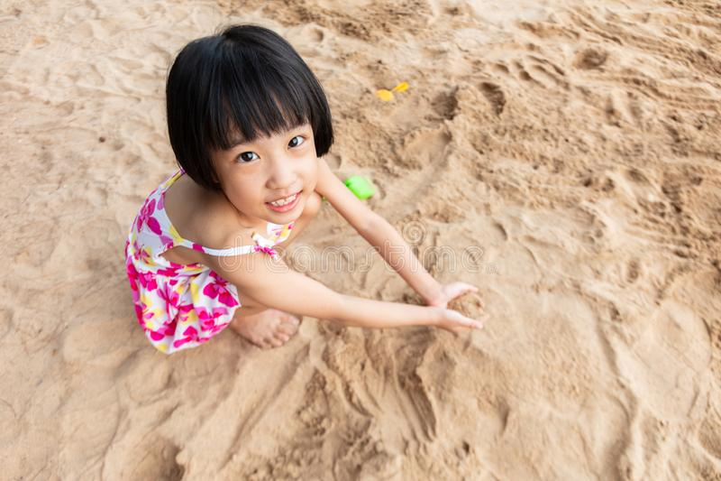 Азиатская китайская маленькая девочка играя песок на пляже стоковые фотографии rf