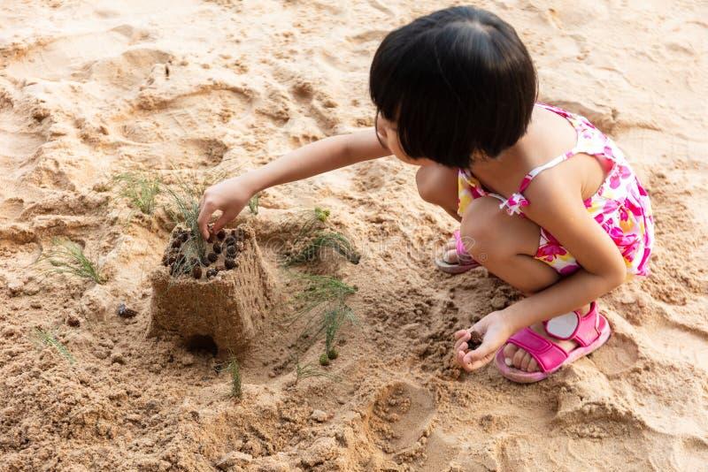 Азиатская китайская маленькая девочка играя песок на пляже стоковое изображение