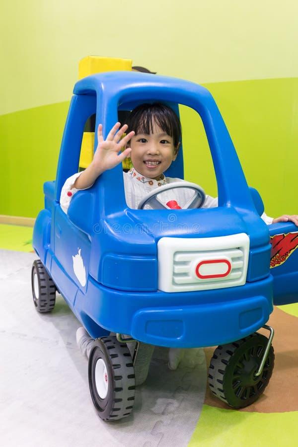 Азиатская китайская маленькая девочка управляя автомобилем игрушки стоковое изображение rf