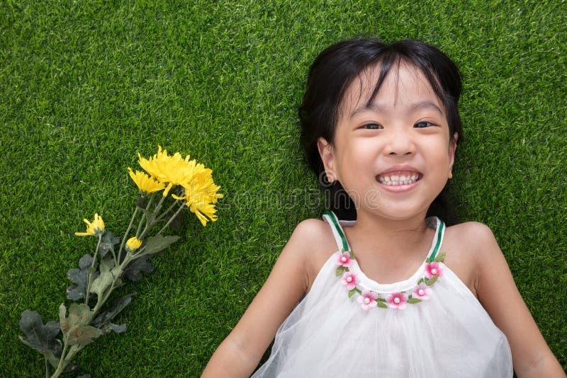 Азиатская китайская маленькая девочка лежа на траве с цветками стоковые изображения rf