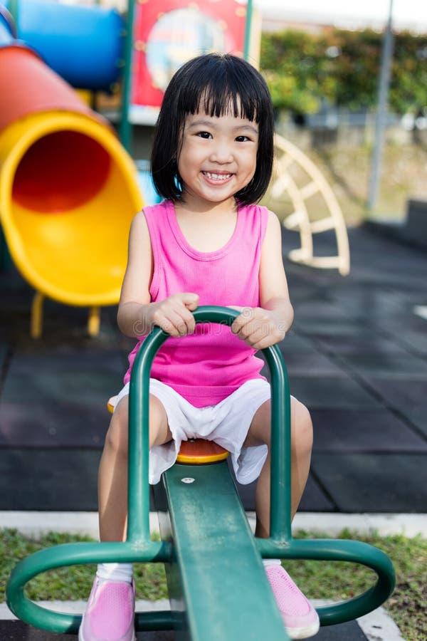 Азиатская китайская маленькая девочка на seesaw на спортивной площадке стоковая фотография