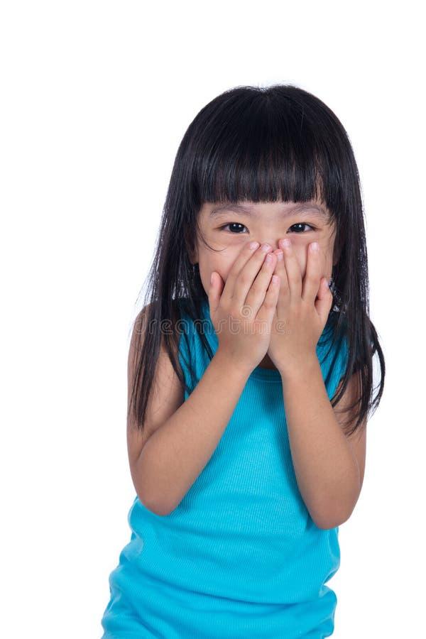 Азиатская китайская маленькая девочка смеясь над и покрывая ее ртом стоковые фото